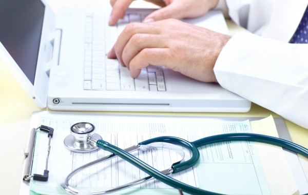 close up image of a doctor using a laptop